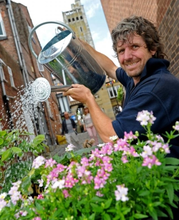 Bob Garner holding a watering can to water pink flowers in front of the Gaskell Memorial Tower
