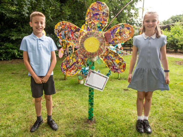 A boy and girl stand next to a decorated flower in their school uniforms