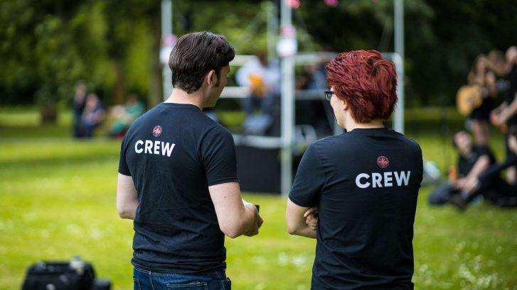 "Two men looking at a stage wearing t-shirts which say ""crew"" on the back"