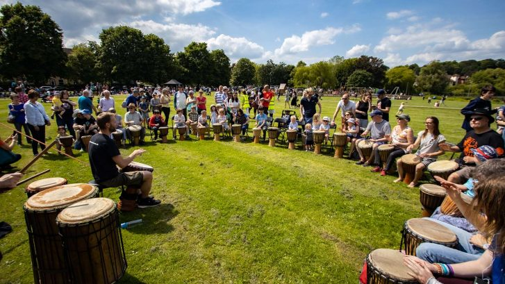 A group sit in a circle playing drums