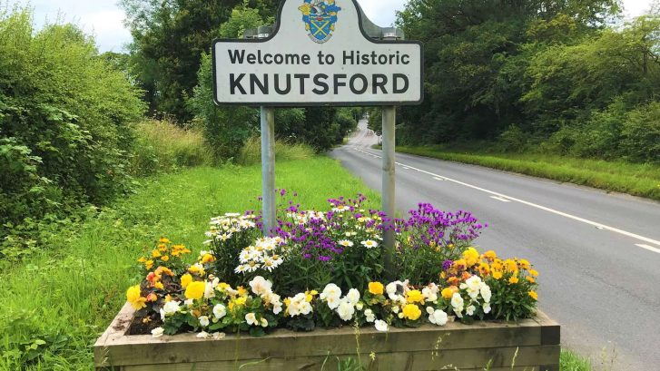 The Knutsford town boundary sign with a floral planter beneath