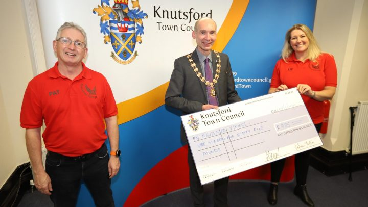 Town Mayor holds large cheque for a charity