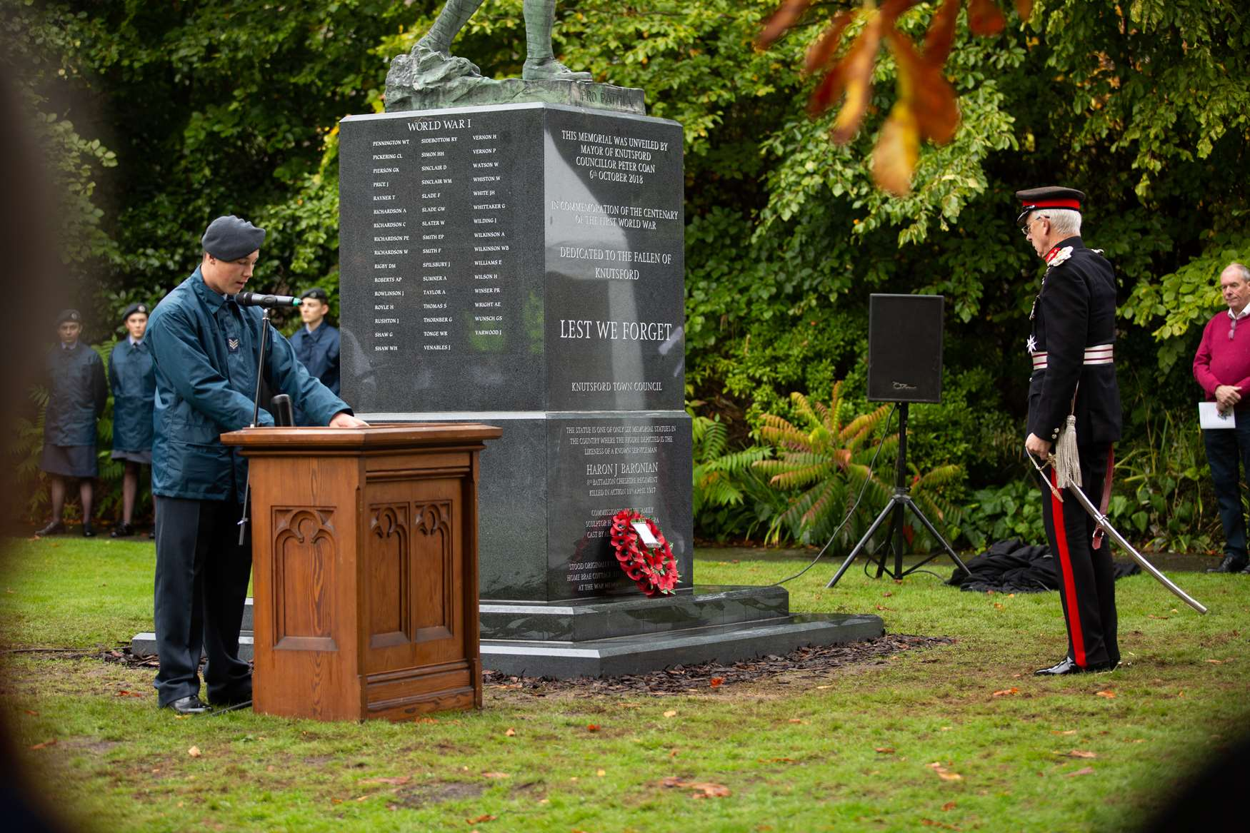 Lord Lieutenant stands at the memorial as a cadet reads from a lecturn