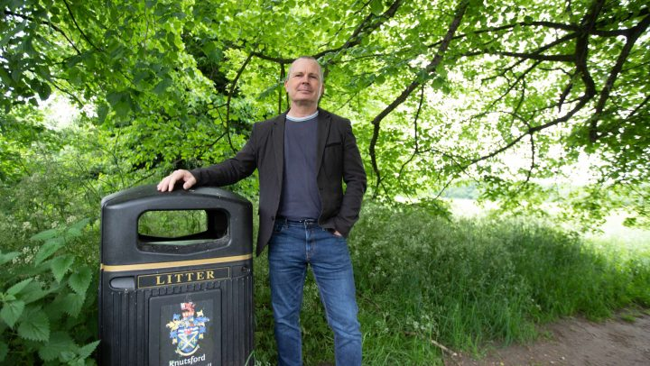Cllr Mike Houghton stands by a bin branded as Knutsford Town Council's against a green leafy background
