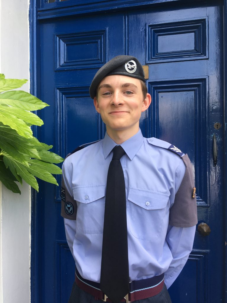 Photo of James Booth, The Mayor's Cadet for 2021-2022 in front of a blue door