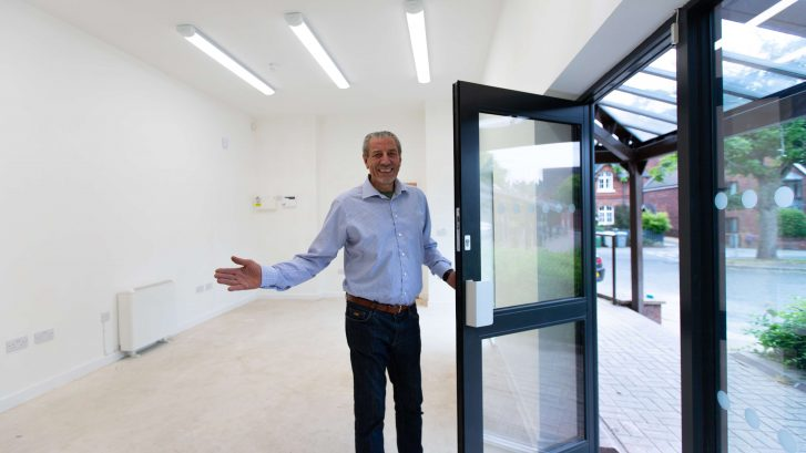 Cllr Peter Coan holds a door open and an arm out welcoming you to a building