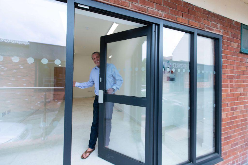 Cllr Peter Coan opens a door.