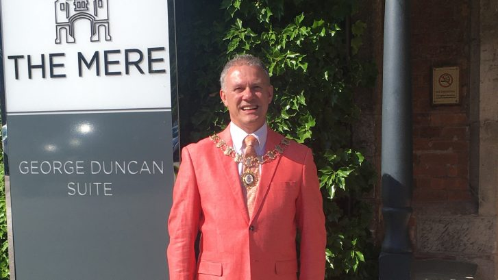 The Town Mayor wearing a bright jacket and the mayor's chain stands outside the Mere Hotel