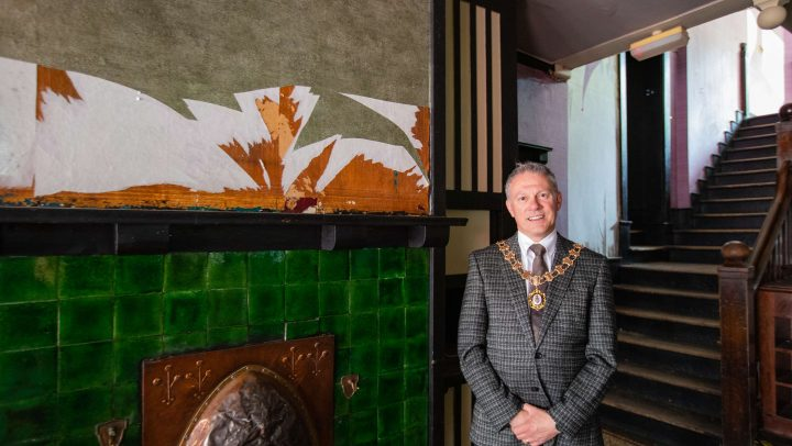 The Town Mayor, wearing his chain of office, stands in 60 King Street where ripped wallpaper can be seen in the foreground