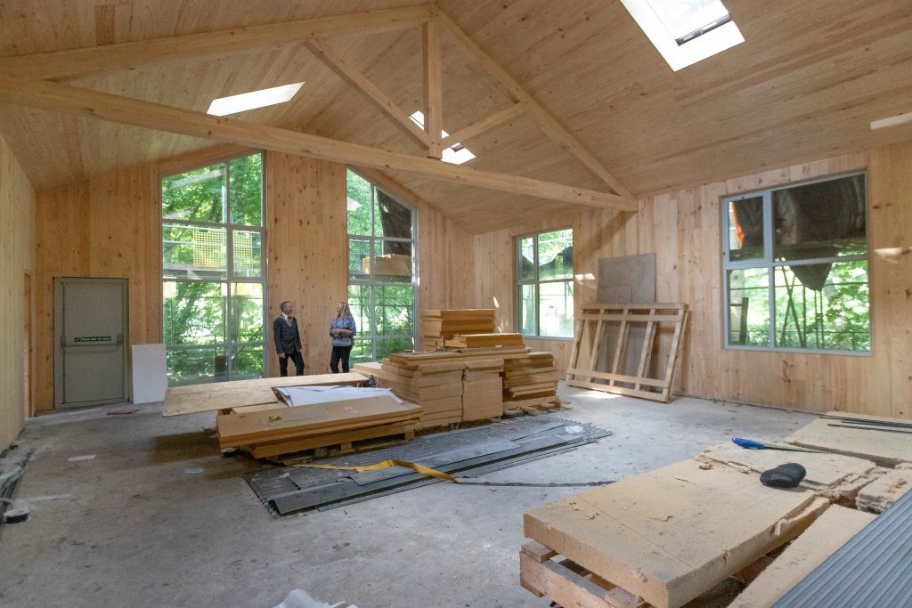 A view of an under construction scout hut whilst two people converse in the background