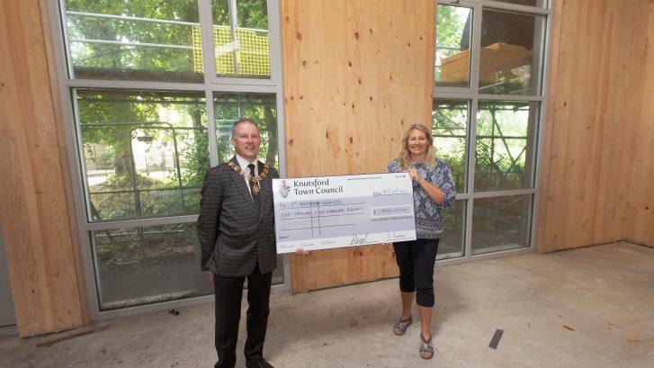 Cllr Stewart Gardiner hands a giant cheque to Lisa Barcroft-Lee