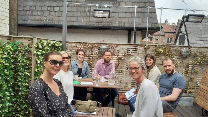 A group of adults in a meeting within a beer garden