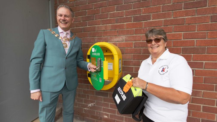 Town Mayor helps put the new defib in place