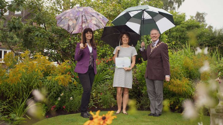 Town Mayor holding an umbrella presenting a certificate to Jackie Edwards who has won the competition