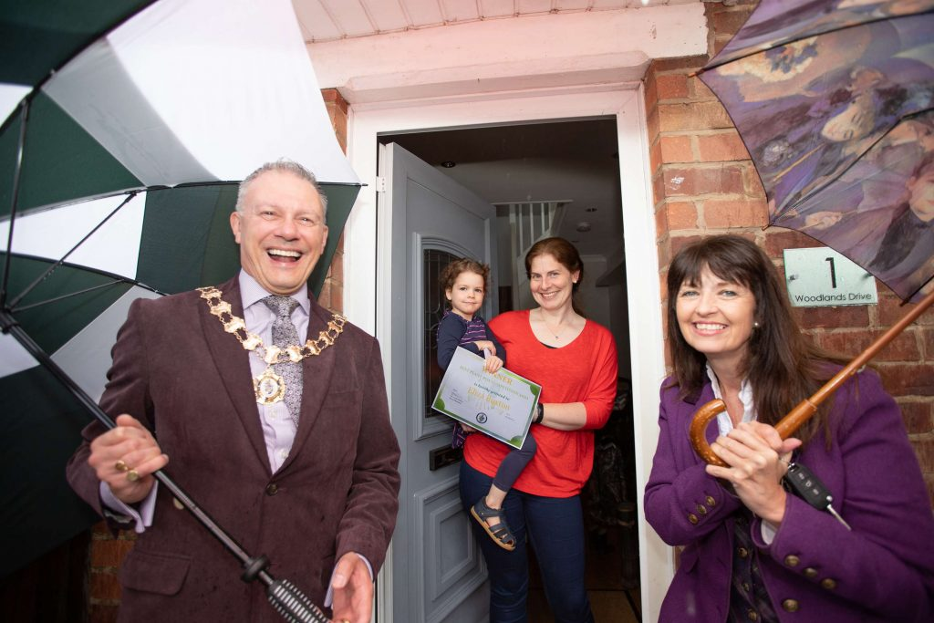 Town Mayor holding an umbrella with the manager of Fryers also holding an umbrella presenting a certificate to a child in its mother's arms stood in a doorway