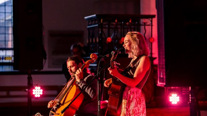A woman plays guitar with a man playing double bass in the background