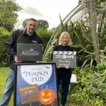 A man holds a sign next to a woman holding a sign in front of a poster for the pumpkin path