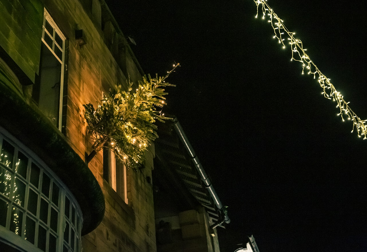 A christmas tree with warm white lights on the front of a stone building